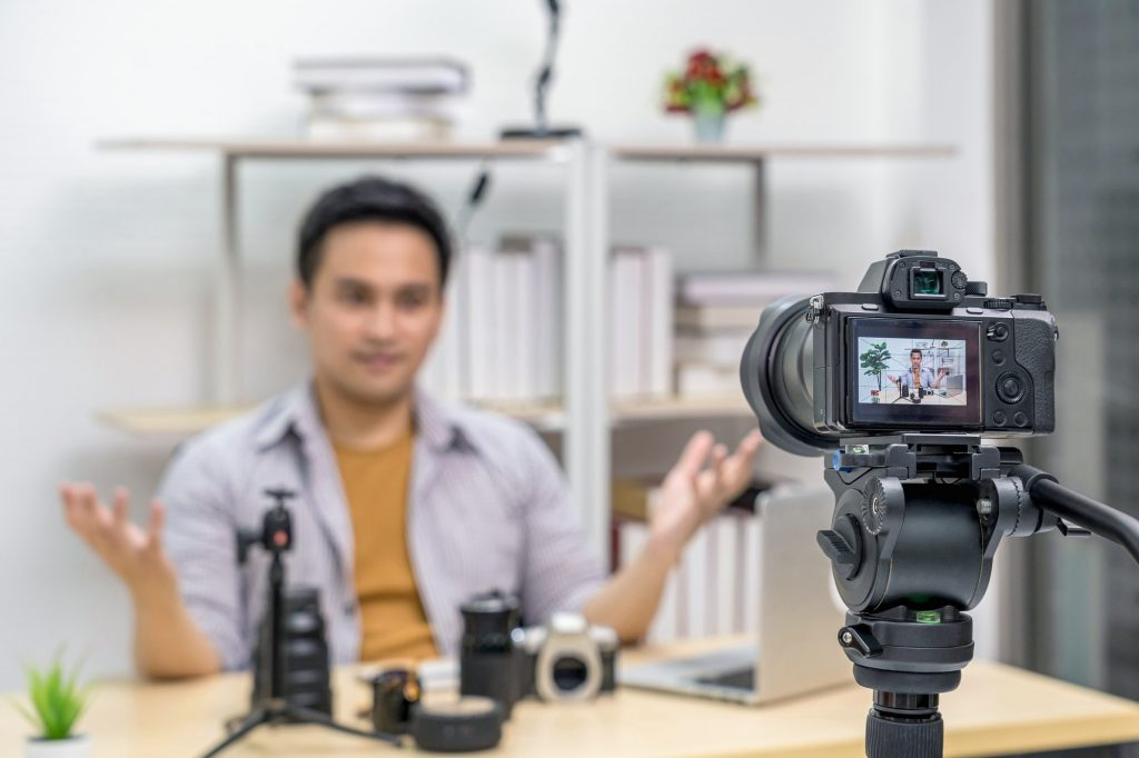 Closeup Camera taking video and live with laptop of Asian Vlogger man satisfied the camera lens